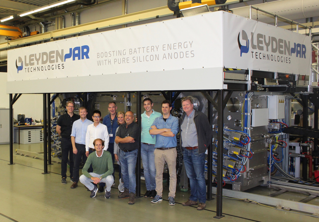 Het team van Leyden Jar met gehurkt Christian Rood, bij de machine in het gebouw in Eindhoven.