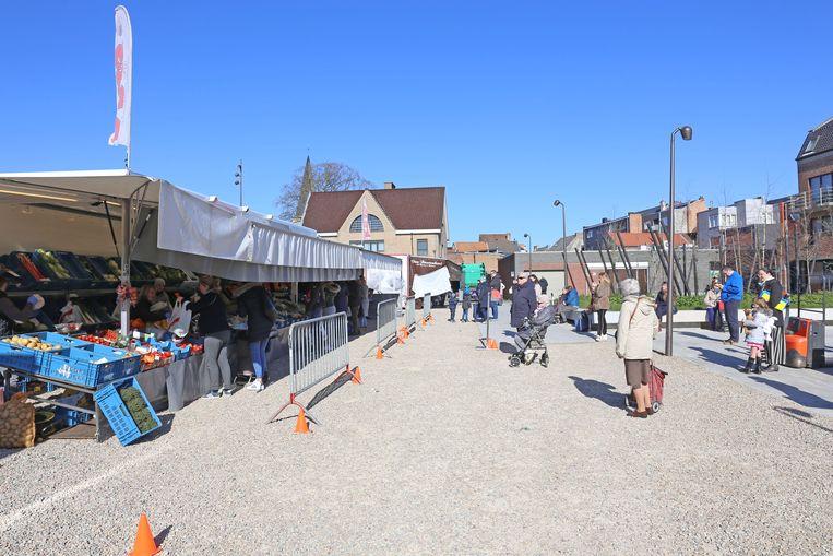 Markt in Asse. De bezoekers wachten in rijen en houden afstand van elkaar.