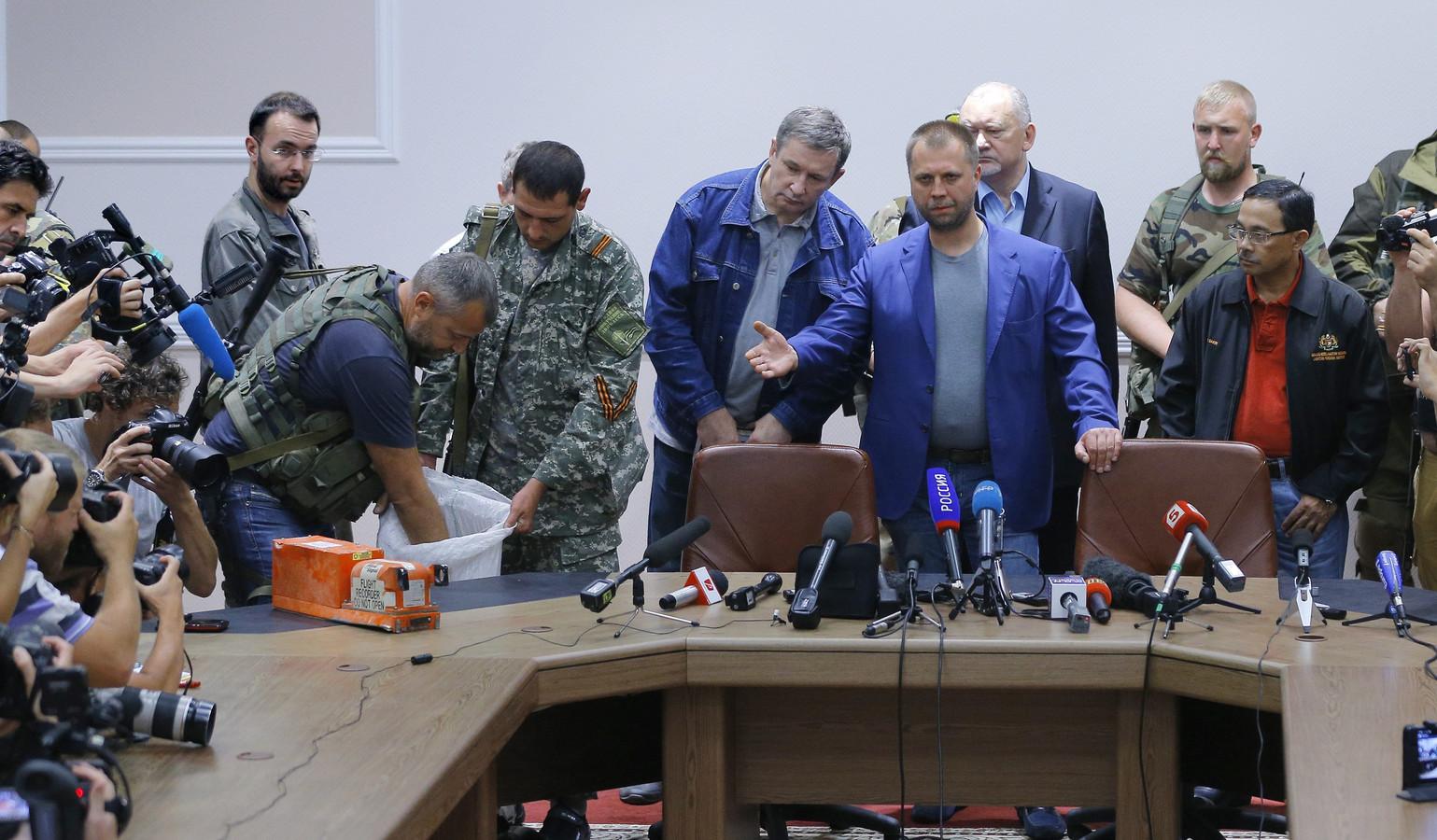 Premier' Aleksandr Borodaj (M) van de zelfuitgeroepen Volksrepubliek Donetsk draagt de zwarte dozen van het rampvliegtuig MH17 van Malaysia Airlines over aan een Maleisische delegatie. In de zwarte dozen worden de vluchtgegevens en de gesprekken in de cockpit opgeslagen.