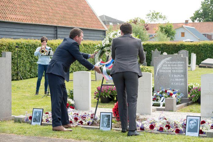Arie Weijler (links) en Niels van Oudenaarde (rechts) leggen een krans bij het graf van Victor Rapley, John Little Brown en Edward Callan op de oude begraafplaats van Sint-Annaland.