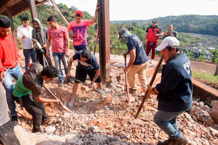 Gewapend met pikhouweel of schep proberen de gravers door het beton te breken.