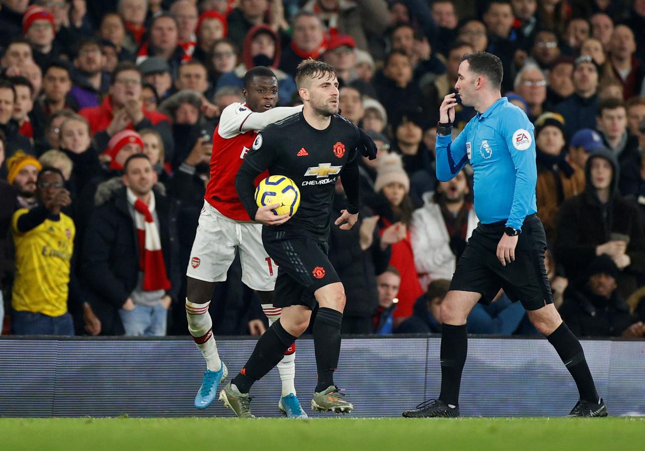 Luke Shaw ontneemt Nicolas Pépé van Arsenal de bal.