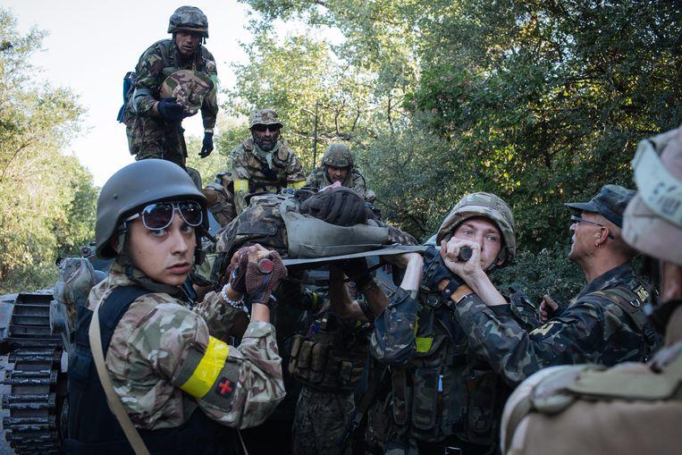 Oekraïense soldaten vervoeren een gewonde militair.  Beeld EPA