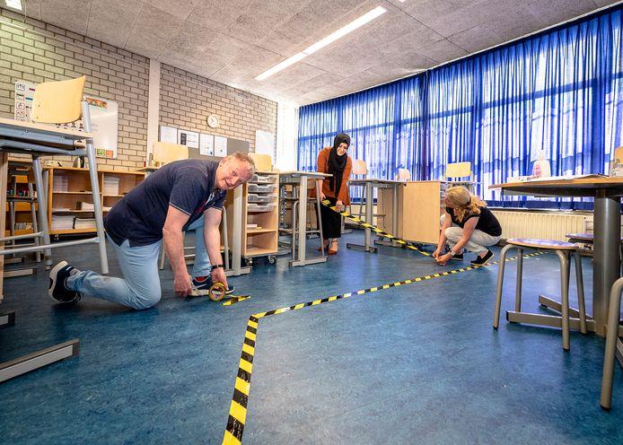 Directeur René Bos en leerkrachten Özlem Karagulle en Jacqueline Hendriks geven met tape aan waar de kinderen van de Pierre Bayle-basisschool wel en niet mogen komen.