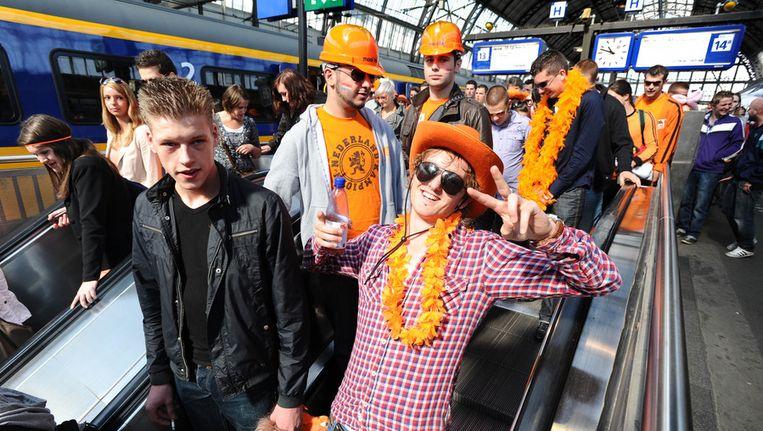 Oranje uitgedoste feestvierders komen aan op Amsterdam CS. Beeld ANP