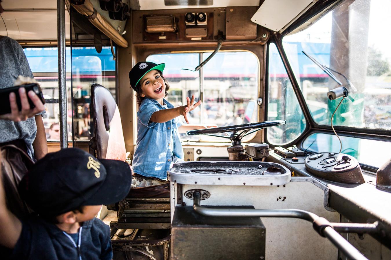 Obi (4 jaar) achter het grote stuur van de oude trolley.