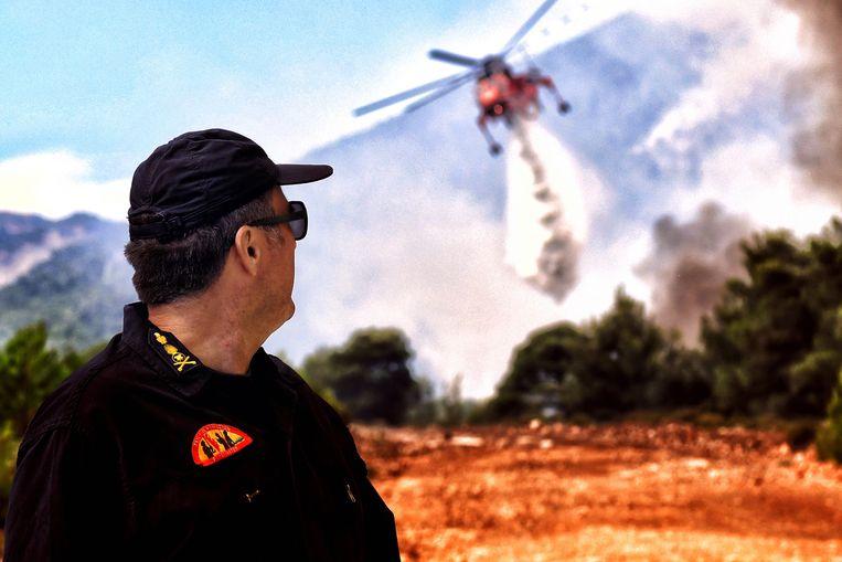 Een brandweerman kijkt toe hoe een helikopter een poging doet een brandhaard te blussen. Drie dorpen en een kinderkamp in Verori, Peloponessos zijn uit voorzorg geëvacueerd. Beeld Vassilis Psomas, EPA