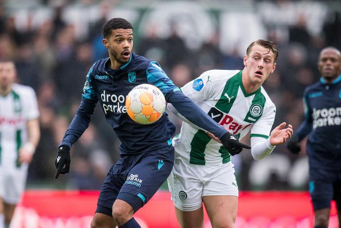 Jake Clarke-Salter (links) voor Vitesse in duel met Kaj Sierhuis van FC Groningen.