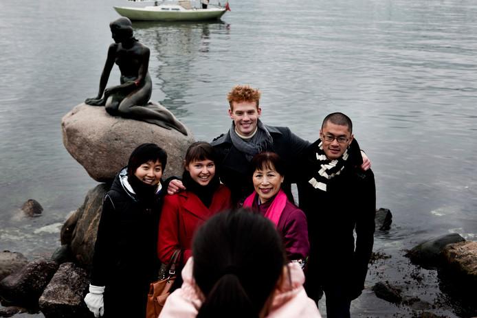 Toeristen voor het wereldberoemde standbeeld de kleine zeemeermin.