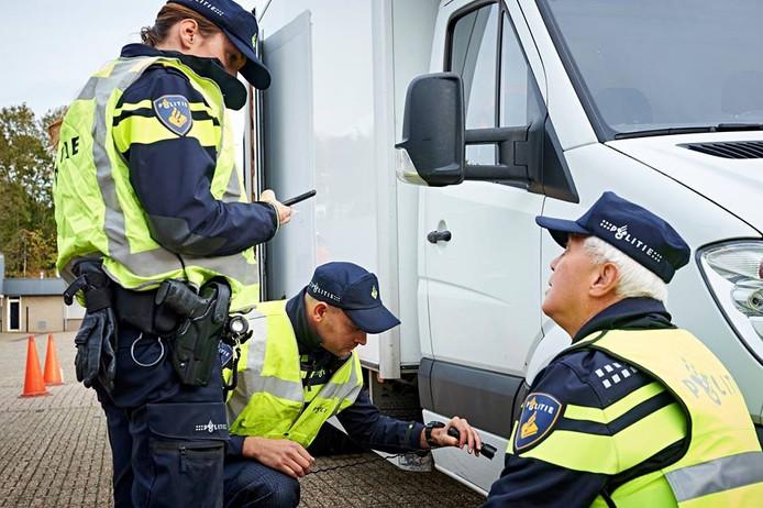 Agenten controleren een voertuig.