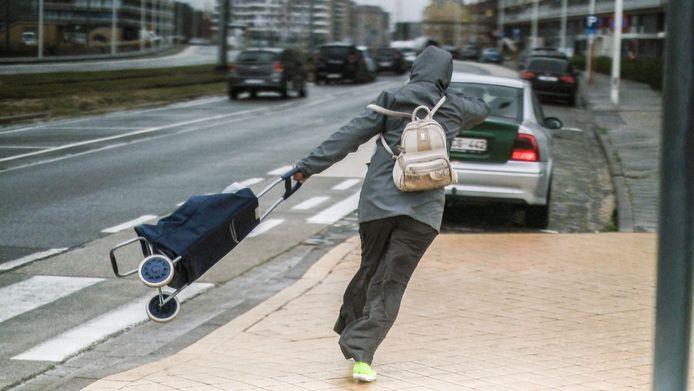 Een wandelaar trotseert de felle rukwinden in Oostende.