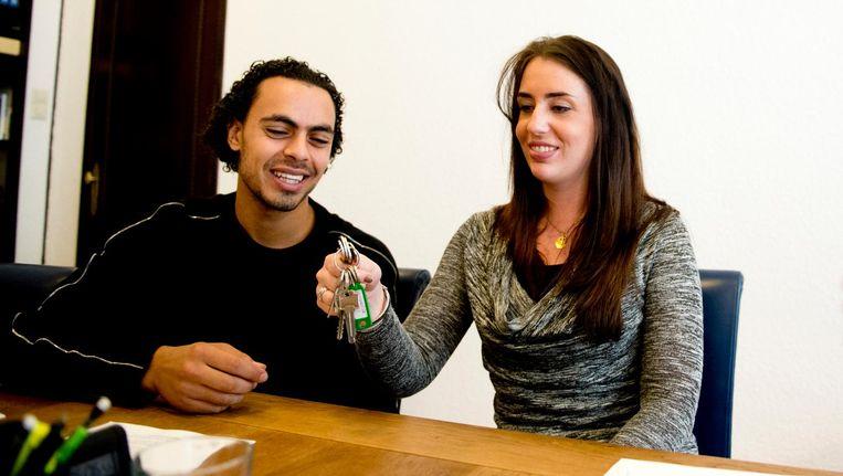 Jonge huizenkopers ontvangen de sleutels van hun woning. Beeld anp