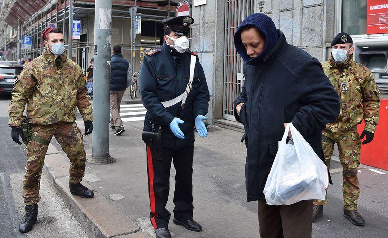 Militairen spreken een man aan in de straten van Turijn.  Beeld EPA