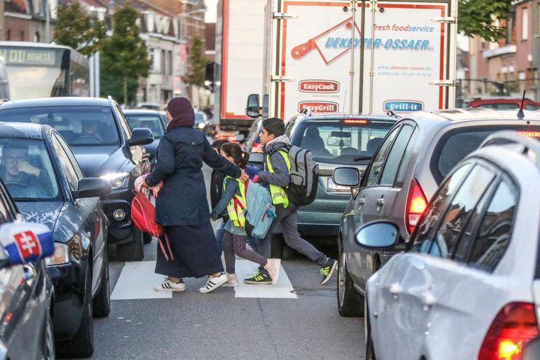 """Een moeder manoeuvreert met haar kinderen tussen de vele auto's op de Oudenaardsesteenweg. """"Er is niemand die zijn kinderen hier alleen laat oversteken"""", klinkt het."""
