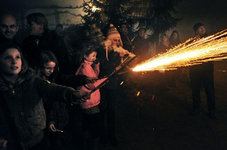 Kinderen steken vuurwerk af op straat.  Beeld Marcel van den Bergh / de Volkskrant