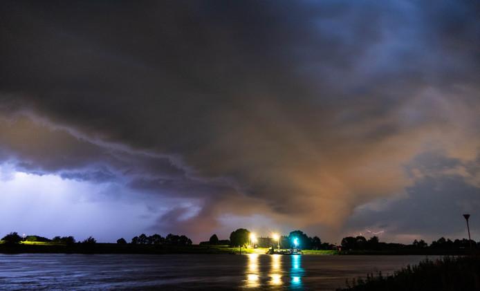 Onheilspellende wolken pakken zich samen boven de IJssel bij Wijhe, op de achtergrond zijn de inslagen te zien.