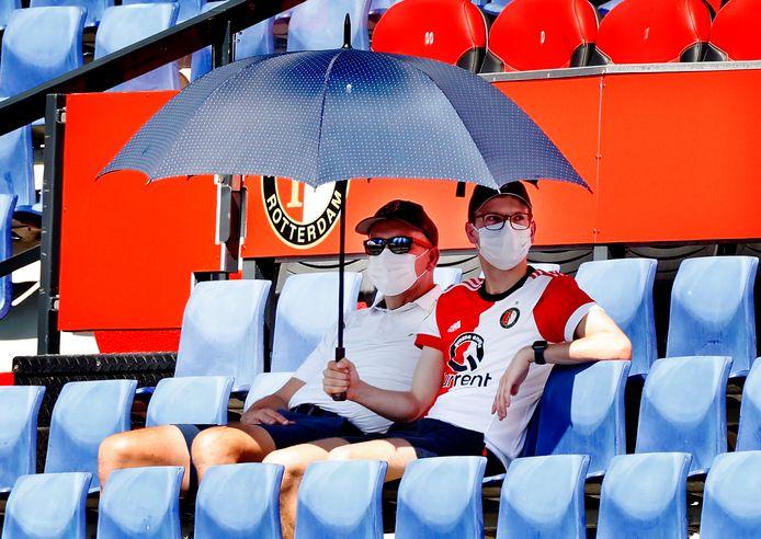 Feyenoord-supporters bekijken het duel met Sparta met mondkapjes.