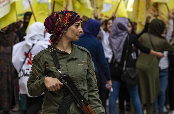 Een Koerdische strijdster beveiligt een demonstratie van Syrische Koerden tegen de Turkse inval.