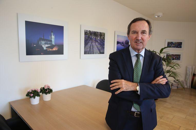 Burgemeester Dirk Pieters (CD&V) in zijn kantoor met op de achtergrond foto's van het Hallerbos en de Sint-Martinusbasiliek, twee onderwerpen waar hij zich binnenkort in wil verdiepen.