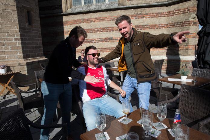 Ajax-fans maken een lolletje met elkaar op het terras op het Simonsplein in Doetinchem. 'Wegwezen', krijgt fan Werenr Burghout te horen, de enige met een Ajax-shirt aan.