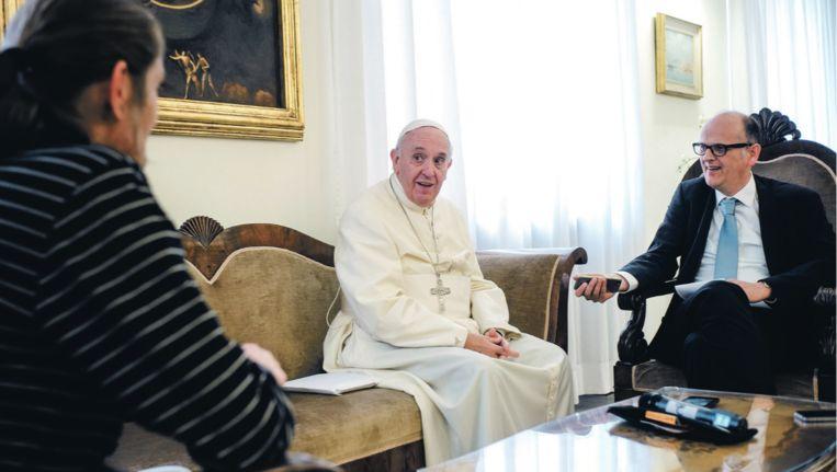 Straatnieuws-verkoper Marc (links) en Trouw-journalist Stijn Fens in Vaticaanstad in gesprek met paus Franciscus. Beeld Frank Dries / Straatnieuws