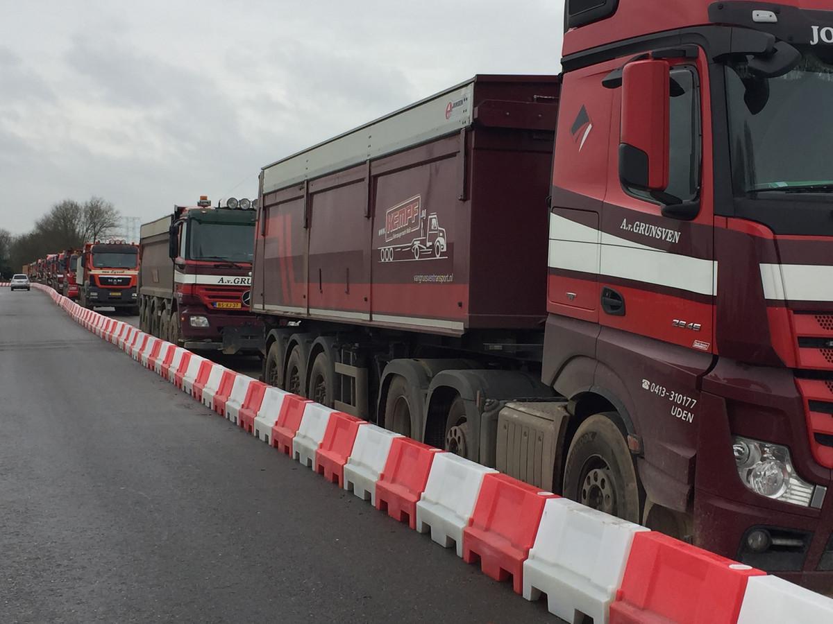 File van vrachtwagens bij Ons Koninsgoord vanwege gedeeltelijke wegblokkade door bewoner Hoolstraat Berkel Enschot