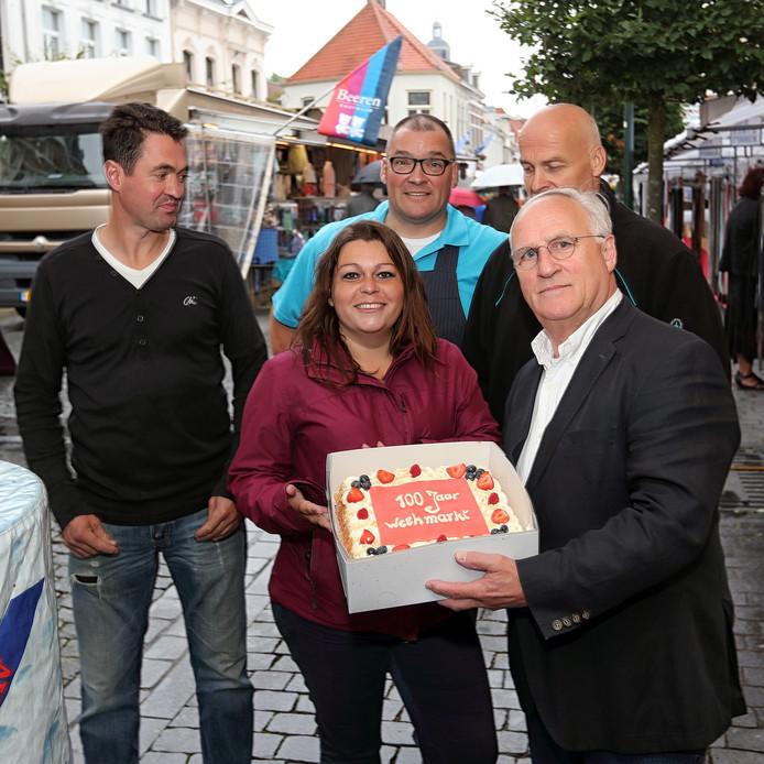 Wethouder Ad Coppens overhandigt taart aan de marktmeester in verband met het jubileum.