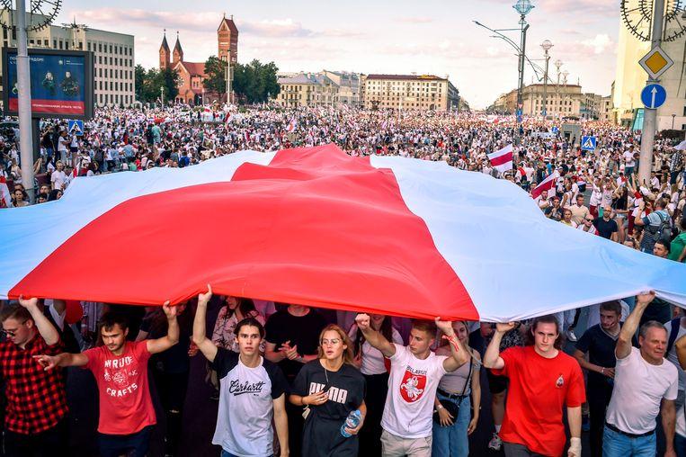 Anti-regeringsdemonstranten gaan in Minsk de straat op met een grote rood-witte vlag om te demonstreren tegen de verkiezingsuitslag waarbij president Loekasjenko, die al 26 jaar aan de macht is, de overwinning zou hebben behaald.  Beeld AFP