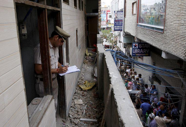 Een politieman schrijft een rapport vanuit het huis waar de elf mensen dood werden teruggevonden.