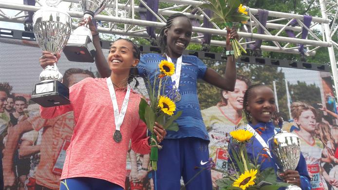 Het blije podium van de 10 km vrouwenloop in Tilburg. Winnares Lonah Chemtai Salpeter temidden van nr twee Selamawit Dagnachew (links) en marathonwereldkampioene Rose Chelimo.