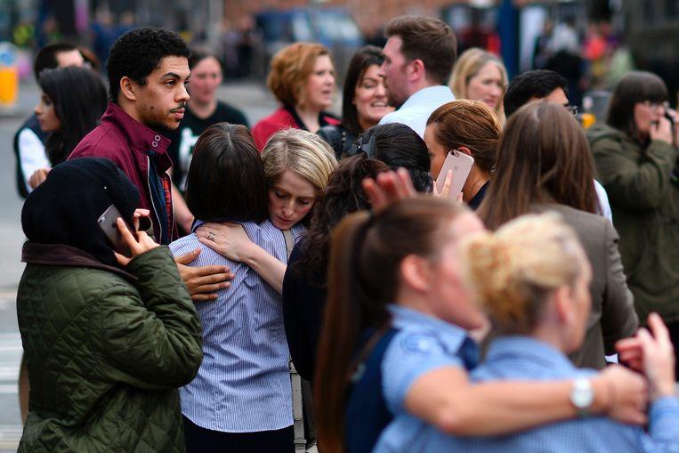 Aanwezigen reageren geschrokken en omhelzen elkaar terwijl de hulpdiensten de gewonden behandelen.