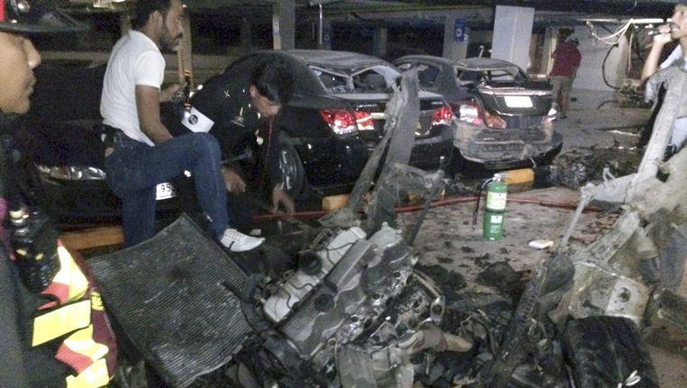 Politie inspecteert het wrak van de auto na de bomaanslag Beeld epa