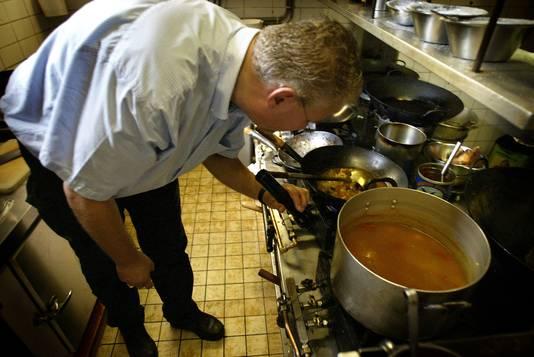 De Inspecteur van de Keuringsdienst van Waren controleert de keuken van een restaurant