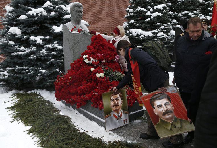Aanhangers van de communistische partij leggen in 2016 bloemen bij het graf van Jozef Stalin bij het Kremlin. De laatste jaren worden weer nieuwe standbeelden van Stalin opgericht. Beeld EPA