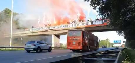 Twente-supporters zwaaien spelersbus uit met vuurwerk