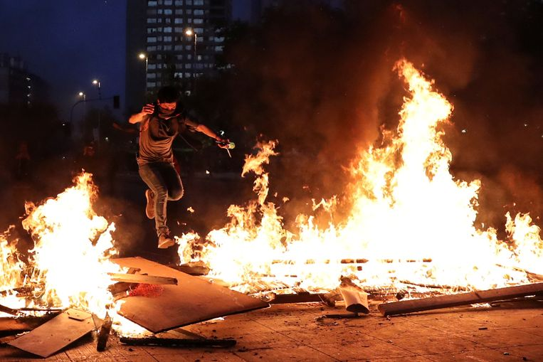 Een demonstrant springt over een brandende barricade in Santiago.