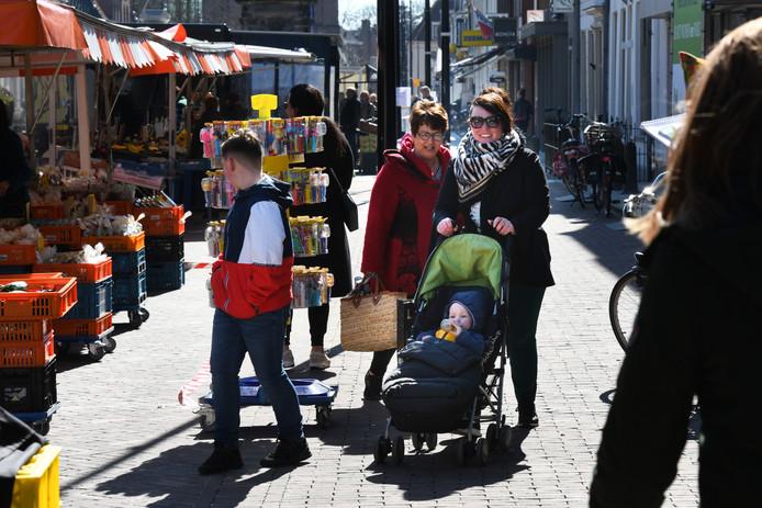 Met melkbussen, afzetlinten en kratten (links) worden de klanten op de markt in Vianen keurig op 1,5 meter van elkaar gehouden.