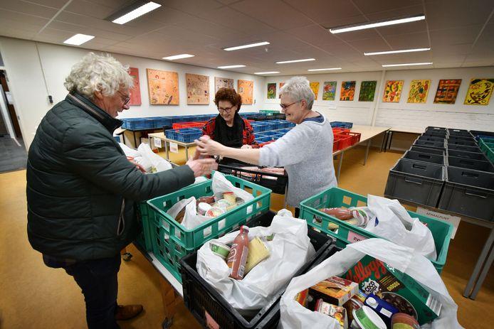 Vrijwilligers van de Voedselbank Oost Twente bezig met het vullen van de voedselpakketten. Die worden nu in een plastic tas in het krat geplaatst, zodat de klanten de tas er uit kunnen pakken. Door toename van het aantal klanten zit de stichting dringend verlegen om nieuwe vrijwilligers.
