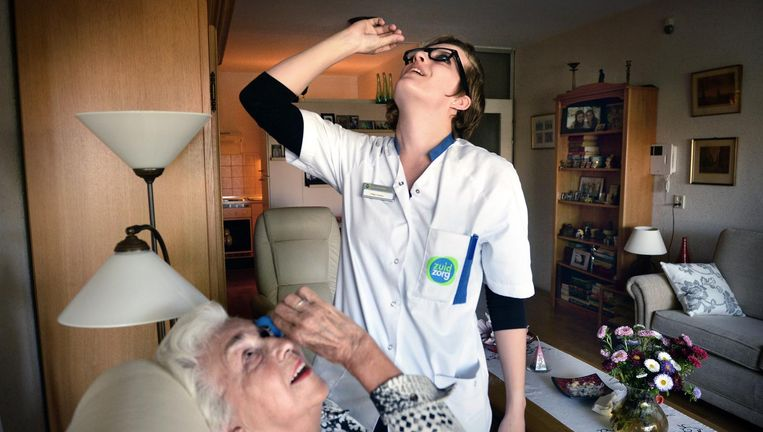 Een medewerker van Zuidzorg leert een cliënt hoe ze voortaan zelf haar oogdruppels kan nemen Beeld Marcel van den Bergh