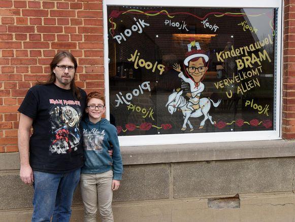 Free Depelseneer en Kinderpauwel Bram bij het versierde raam van zijn café.