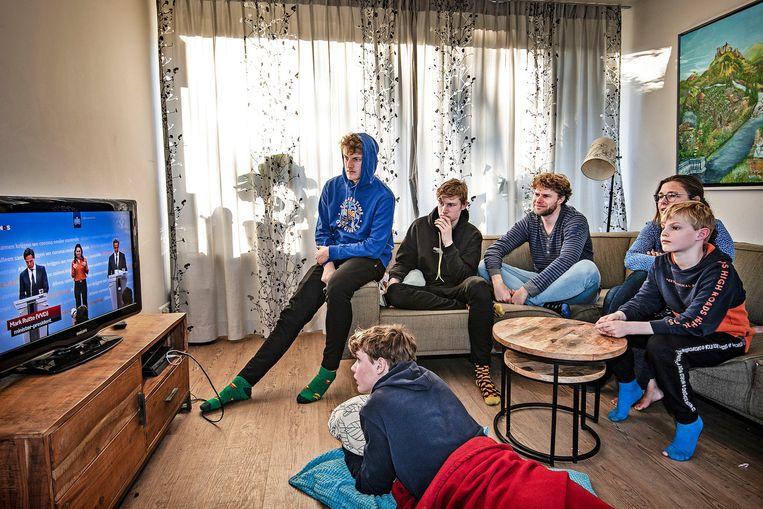 Het gezin De Bree kijkt naar de tv-uitzending waarin premier Rutte bekendmaakt dat de beperkingen nog tot en met 28 april gaan duren.  Beeld Guus Dubbelman / de Volkskrant