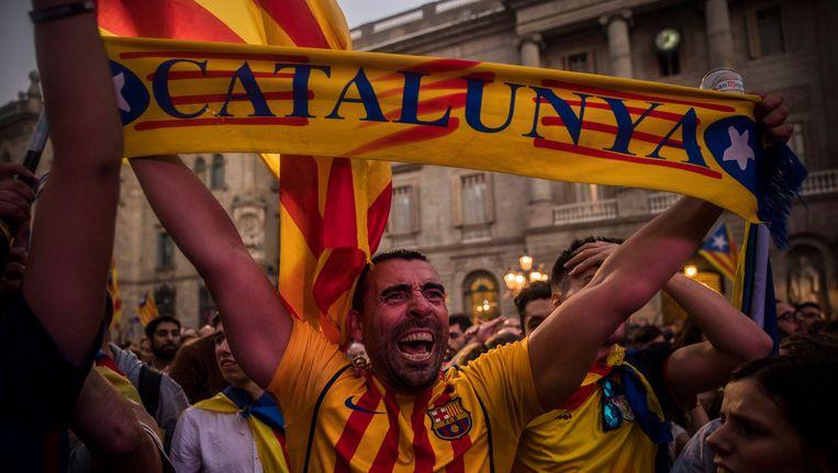 Voorstanders van een onafhankelijk Catalonië staan juichend op straat in Barcelona nadat de regionale regering de onafhankelijkheid heeft uitgeroepen. Beeld ap