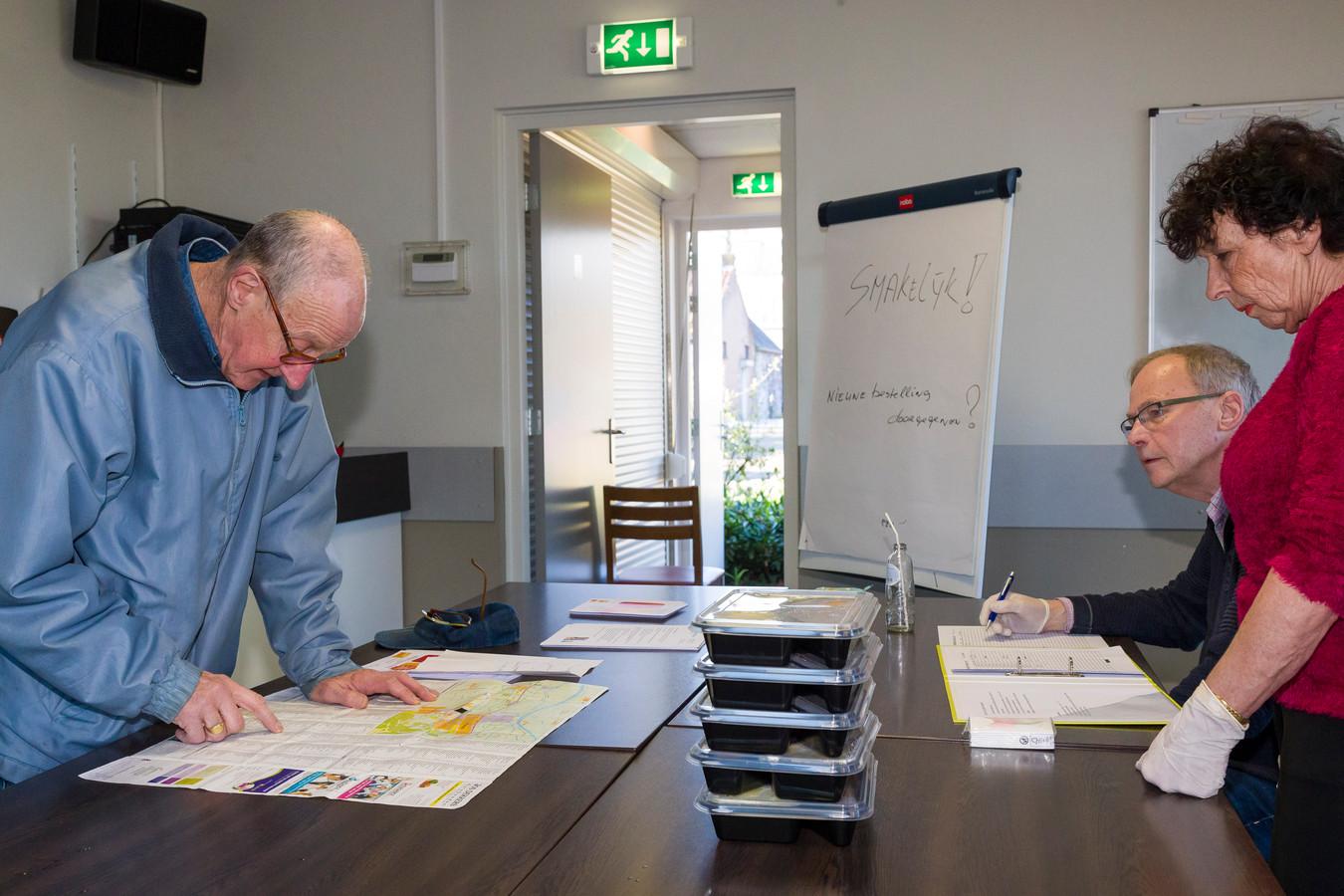 Omdat niet alle klanten in staat zijn zelf hun maaltijd te komen halen, gaat vrijwilliger Hennie Bekker (links) het eten brengen. Met de kaart erbij kijkt hij wat de beste route is.