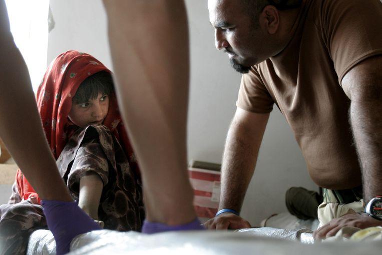 Een Afghaans meisje met een tolk in het Nederlandse kamp Deh Rawood in 2006. Beeld anp