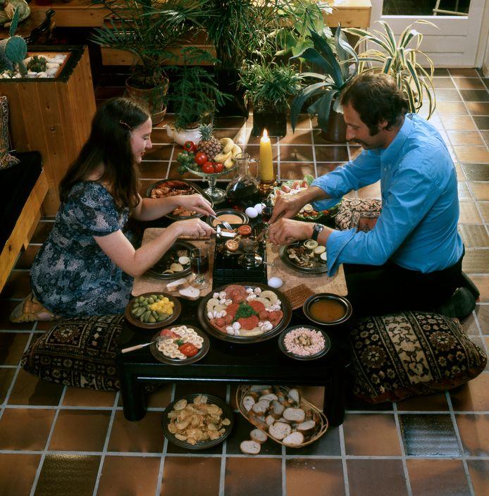 Gourmetten in 1974. Jong echtpaar bakt op een gourmetstel in kleine pannetjes.