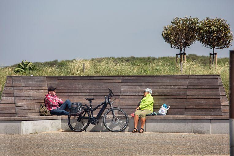 Vlakbij het strand zijn enkele mensen te vinden die ondanks de harde wind proberen van de zon genieten. Twee ouderen op gepaste afstand op een bankje. Beeld Arie Kievit