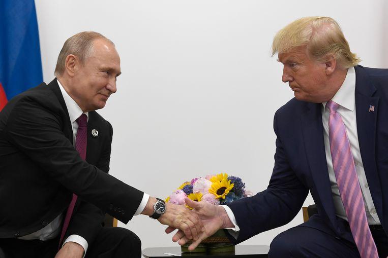 Een handenschudmoment tussen president Donald Trump en president Vladimir Poetin, op de G-20-top in Osaka, Japan.  Beeld AP