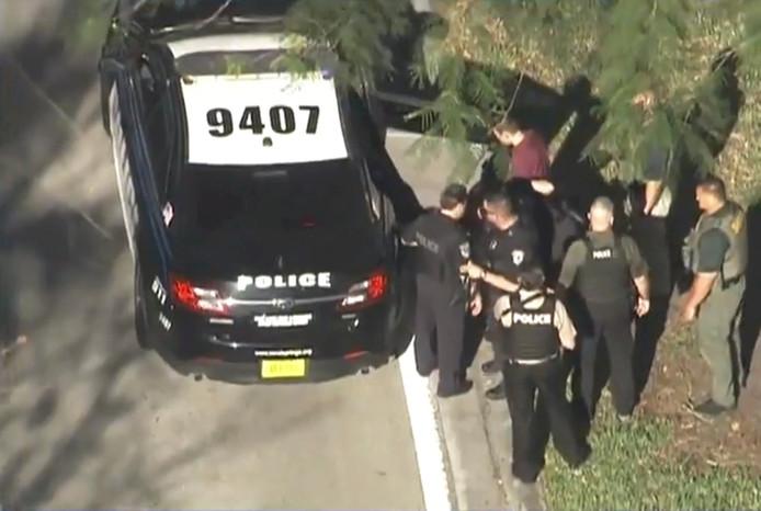 De verdachte wordt weggeleid naar een politieauto.