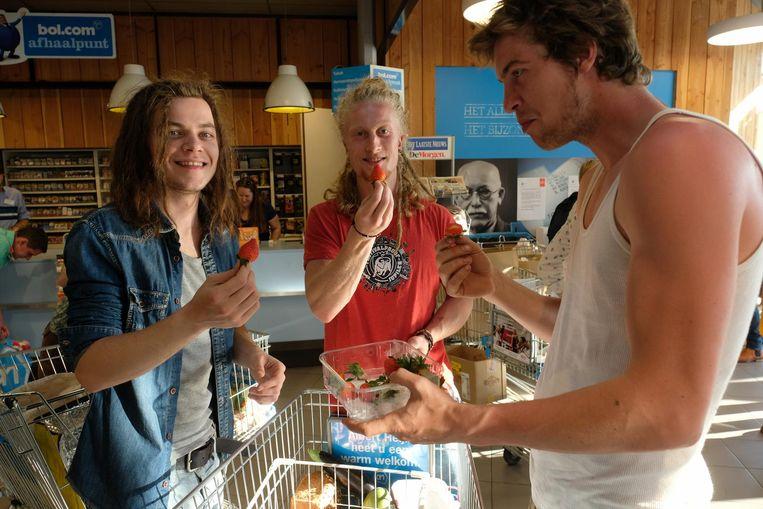 Twintigers Jelle, Janosh en Jappe eten de aardbeien, in een plastic doosje, nog in de winkel op.