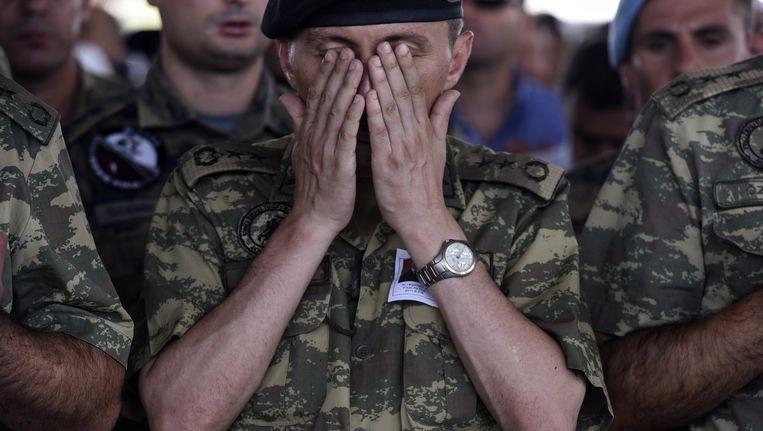 Een Turkse soldaat bidt tijdens de begrafenis van een collega die deze week om het leven is gekomen bij gevechten langs de grens met Syrië. Beeld afp